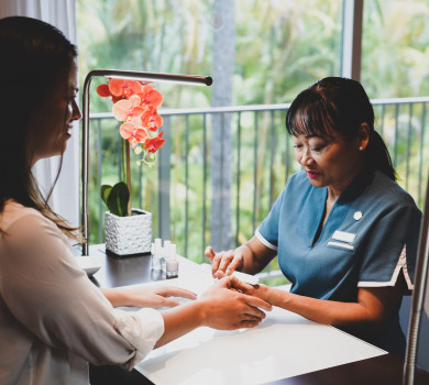 woman enjoying personal nail file manicure in spa